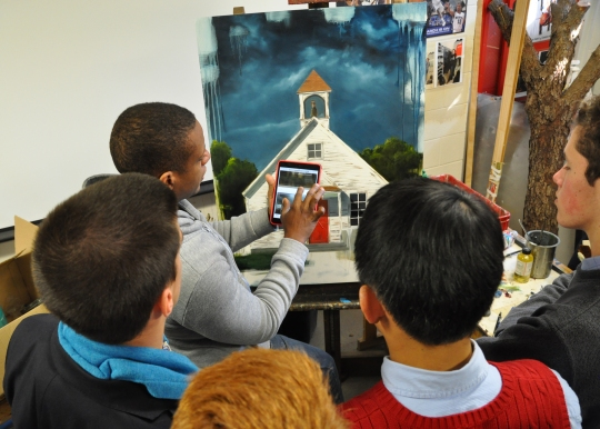 Artist Mr. Jared Small demonstrates the use of new technology with his painting of an old-fashioned schoolhouse.